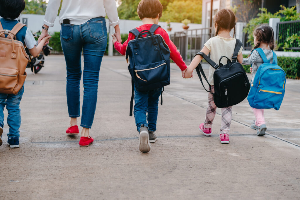 Back to School of Mother and pupil and kids holding hands going to school