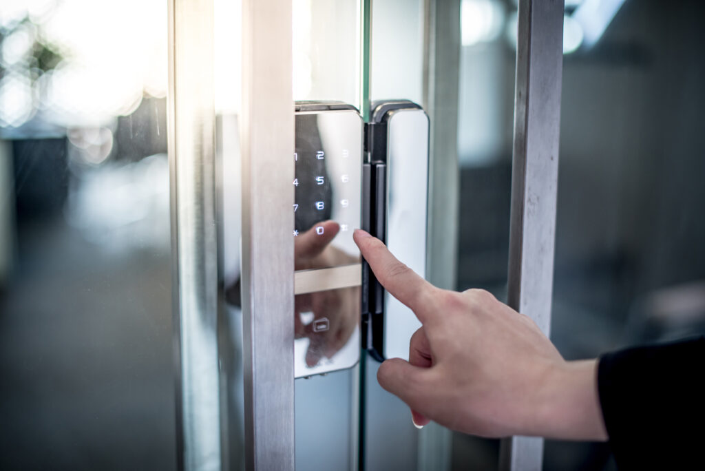 Businessman hand pressing down password number on electronic access control machine to open the office door. Security system concept