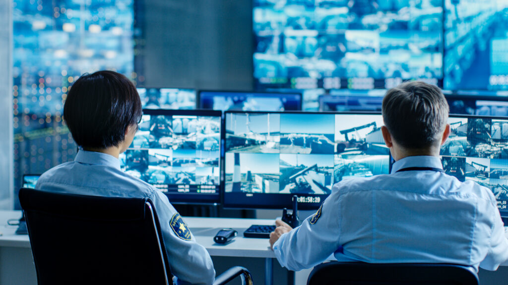 In the Security Control Room Two Officers Monitoring Multiple Screens for Suspicious Activities, They Report any Unauthorised Activities. They Guard Object of National Importance.