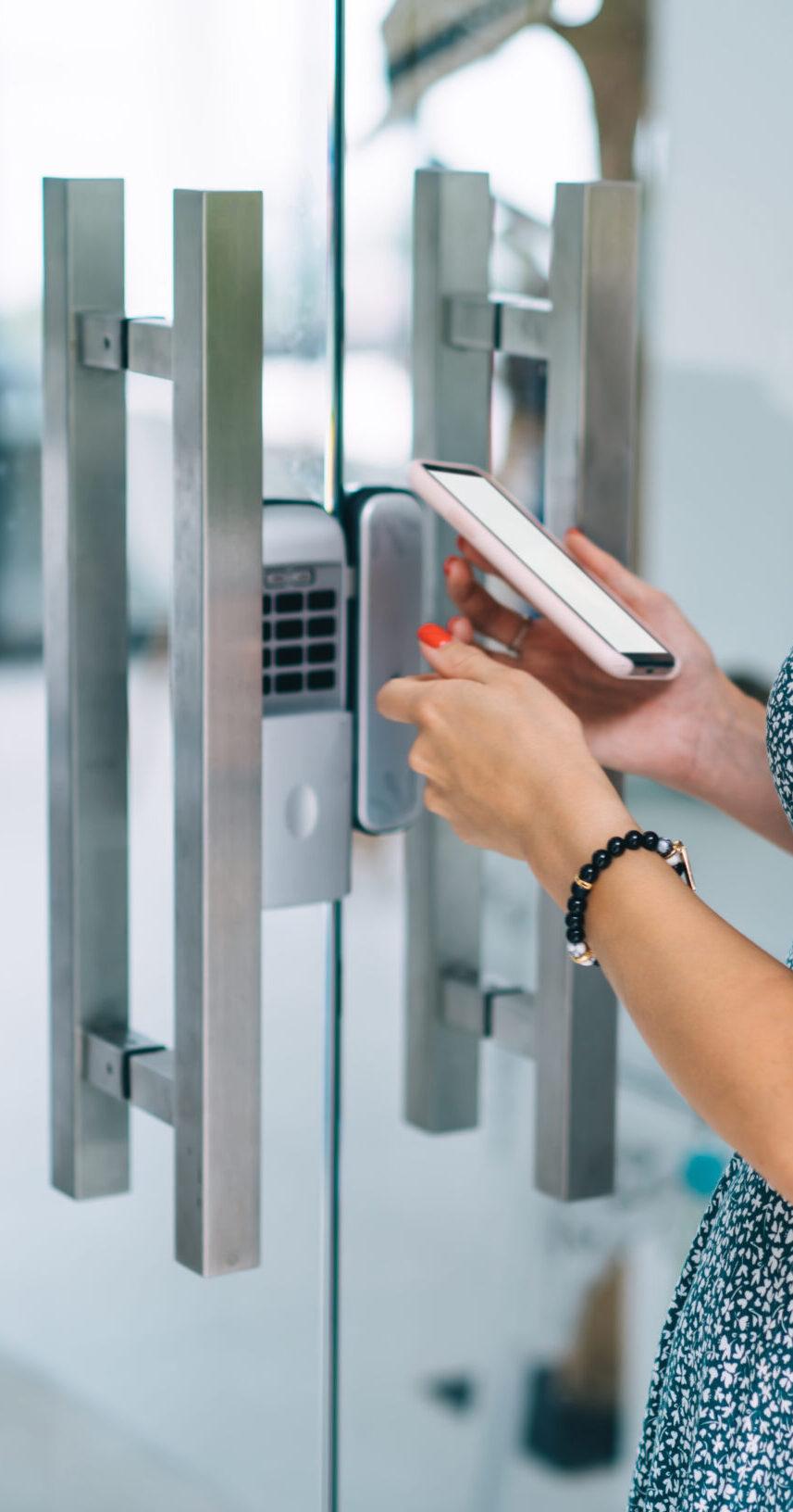Young female unlocking door by smartphone